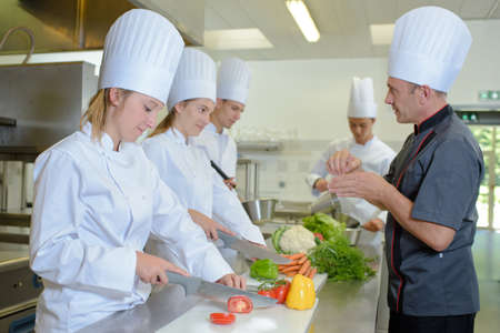 trainees: Chef watching trainees at work Stock Photo