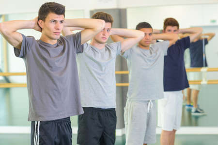 arms behind head: Four young men exercising, arms behind their heads Stock Photo
