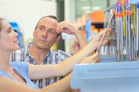 sceptical: Lady choosing drill bit, man looking sceptical