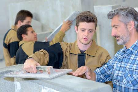 leveler: Teacher showing apprentice how to float cement