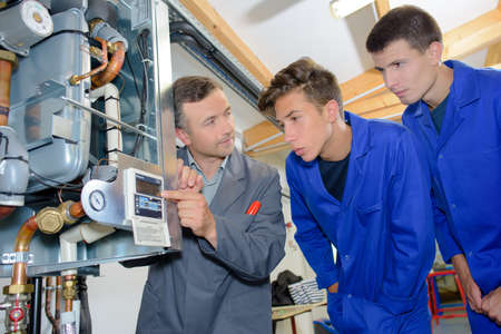two men: Man looking at digital display on boiler with two apprentices Stock Photo