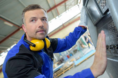 machine tool: Workman with hand hovering over machine Stock Photo