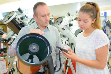 astronomic: Man and young lady in telescope shop Stock Photo