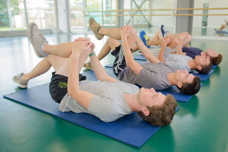 knees bent: Four men on floor exercising, leg bent