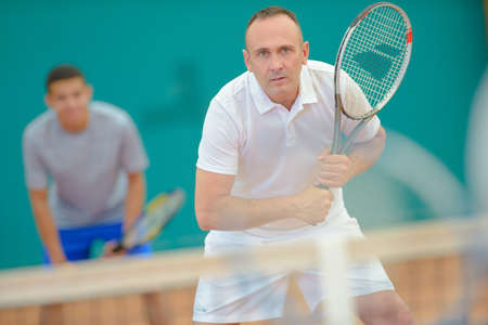 poised: Men playing doubles tennis Stock Photo