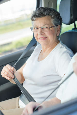 Elderly lady putting on her seatbelt Stock Photo