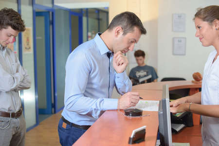 Man filling out a form stood at reception desk Фото со стока