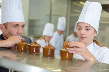 ramekin: Two chefs looking in ramekin pots Stock Photo