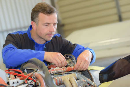 aircraft: Man working on wiring of aircraft