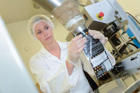 higiene: Mujer operativa fábrica llenar la bolsa de la máquina Foto de archivo