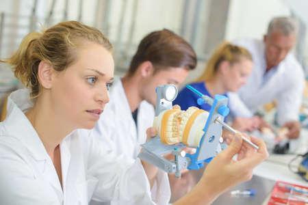 Weibliche Techniker hält Zahnersatz in einer Klemme Standard-Bild - 49309191