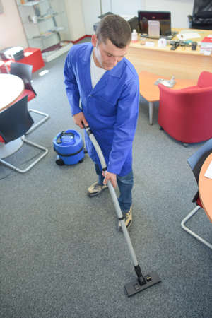 service industry: Man vacuuming office