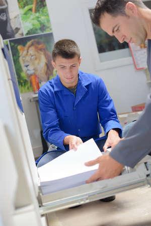 fotocopiadora: Dos hombres Carga de papel en la fotocopiadora