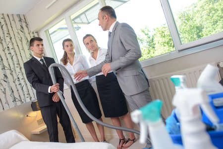 Supervisor with team of cleaners in hotel room Stock Photo