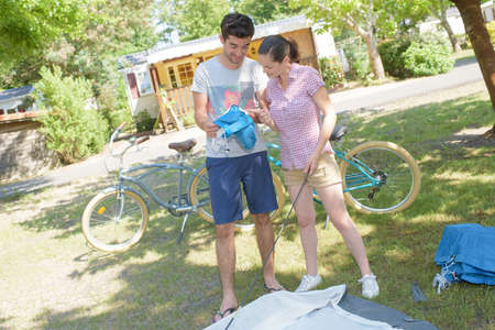 erecting: Couple erecting a tent Stock Photo
