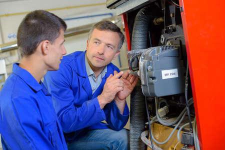 Tradesman erklären Maschinen in die Lehre Lizenzfreie Bilder