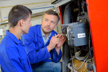 Tradesman explaining machinery to apprentice Фото со стока