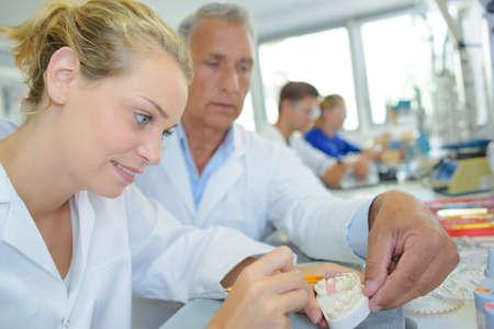 guiding: Supervisor guiding dental technician Stock Photo