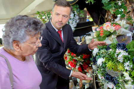 grieving: Undertaker helping woman choose flowers