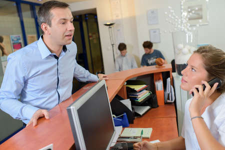 impatient: Man at reception, receptionist on telephone