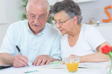 persona mayor: Pareja de ancianos mirando de la revista y tomando notas Foto de archivo
