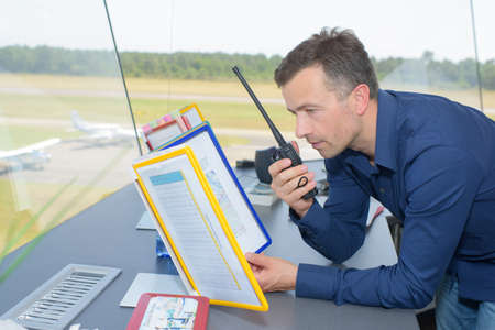 two way: Man in control tower talking into two way radio Stock Photo