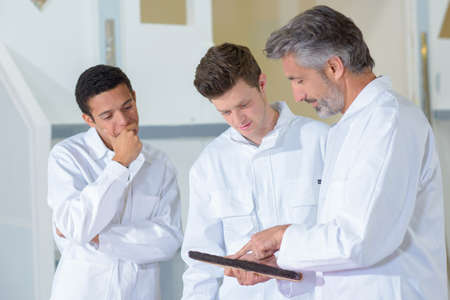 white coats: Three men in white coats looking at clipboard