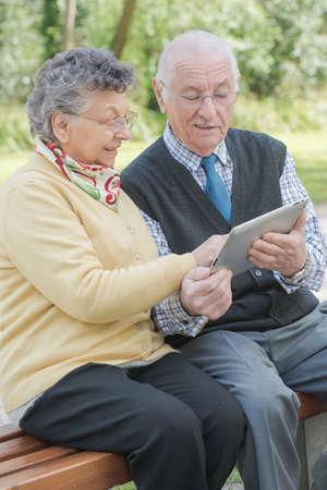 persona mayor: pareja de ancianos con la tableta Foto de archivo