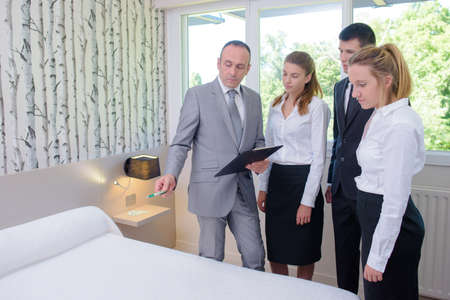 hotel staff: Supervisor in bedroom instructing hotel staff
