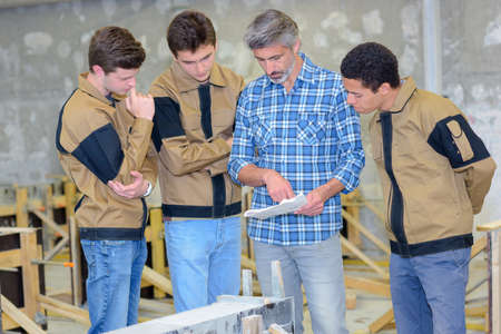 practical: Apprentices reading plans held by instructor