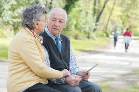 android tablet: Elderly couple in park looking at tablet