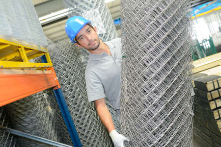 chain link fence: Man holding roll of metal fencing wire Stock Photo