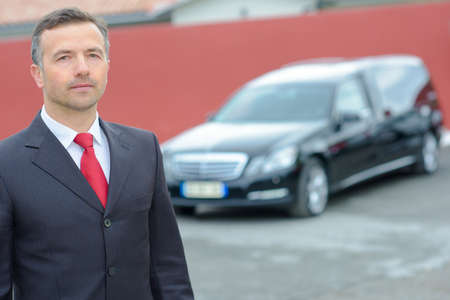 procession: Portrait of funeral director standing in front of hearse