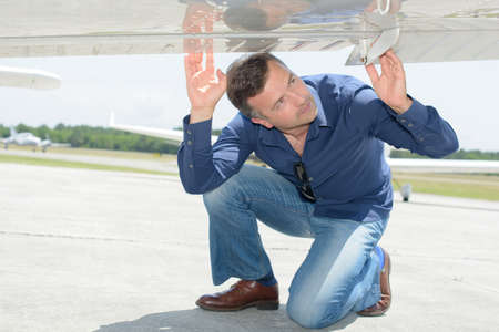 crouched: Man looking at underside of aircraft Stock Photo