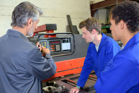 demonstration: Man explaining workings of machine to two students