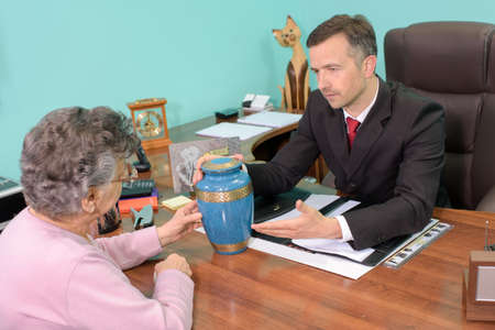 urn: Funeral director with woman, looking at urn Stock Photo