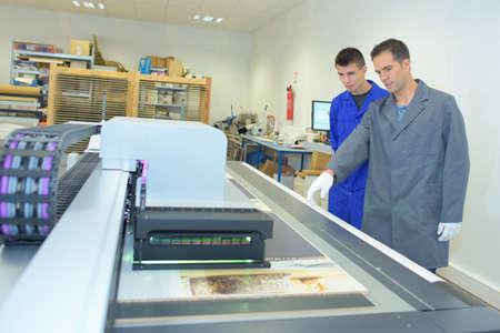 imprenta: Dos hombres en trabajos de impresión profesional