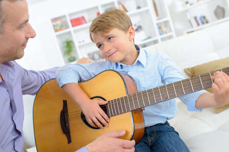boy playing guitar: Young boy playing guitar to father