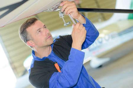the maintenance: Hombre que trabaja en la parte inferior de una aeronave Foto de archivo