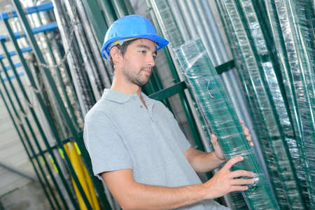 shrink wrapped: Man selecting shrink wrapped pack of poles Stock Photo