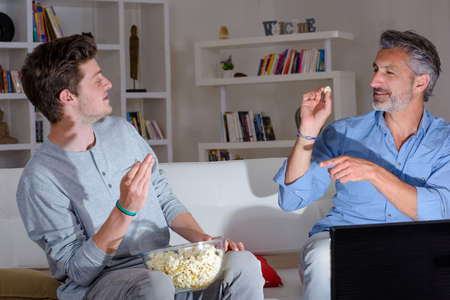 eachother: Father and son aiming popcorn at eachother Stock Photo
