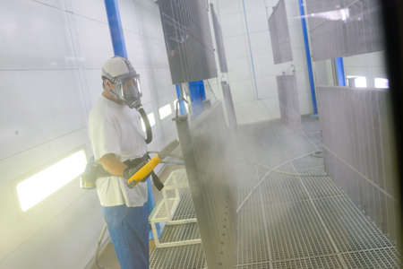 Man sandblasting metal grid