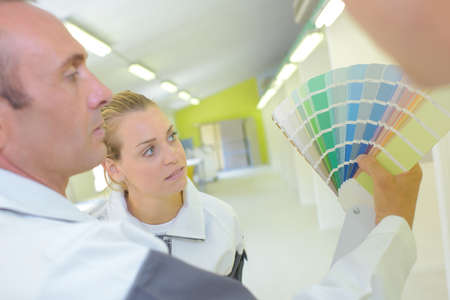 confer: Man and lady looking at paint charts