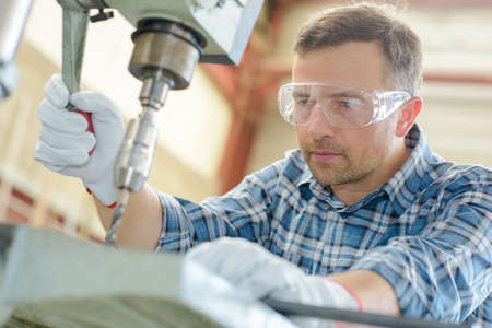 drill: Workman using bench drill Stock Photo