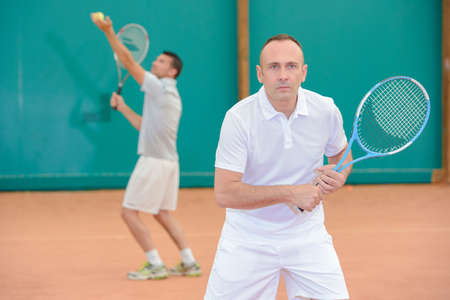 serf: Two men playing doubles tennis Stock Photo