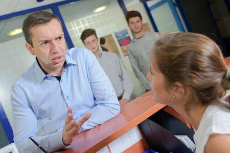 Man at reception desk getting angry Foto de archivo