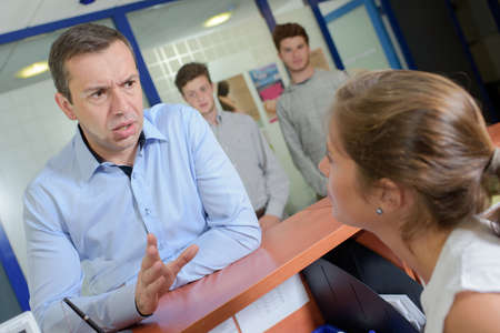 hassle: Man at reception desk getting angry Stock Photo