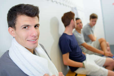changing room: Young men sat in changing room Stock Photo