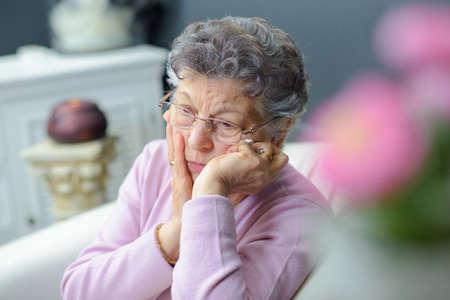 forlorn: Forlorn elderly lady sitting alone Stock Photo