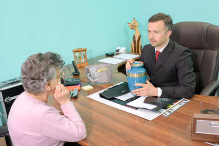 formalities: Funeral director in meeting with woman, holding an urn